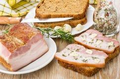 三明治用烟肉和大蒜、刀子、迷迭香、面包和香料 免版税图库摄影