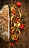 三明治用熏制的绵羊乳酪、烤夏南瓜、蕃茄和草本在一张木土气桌上 图库摄影