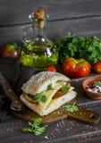 三明治用蕃茄和乳酪,供食在黑暗的木表面上的一个切板 库存照片