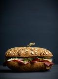 三明治用谷物面包、火腿、蕃茄和水芹在黑暗的背景 免版税图库摄影