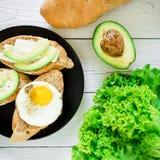 三明治用鲕梨和鸡蛋在一块黑暗的板材在土气背景 平的位置 顶视图 素食主义者的鲜美早餐 库存照片