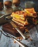 三明治用鸡蛋、蕃茄、葱和烟肉在木的葡萄酒 库存照片