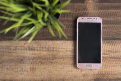 三星J3赞成智能手机投入了木桌背景 免版税图库摄影