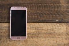 三星J3赞成智能手机投入了木桌背景 免版税库存图片