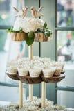 三有排列的木显示用杯形蛋糕 库存照片