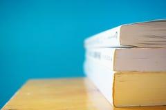 三本书在蓝色背景中 免版税库存图片