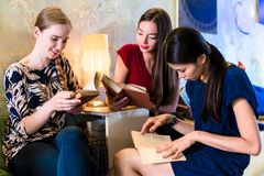三本少妇阅读书在一个现代地点 免版税库存照片