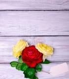 三朵开花的玫瑰和一个白皮书标记 免版税库存照片