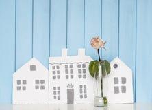 三朵木房子和白色玫瑰在书架 库存图片