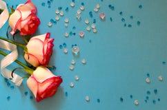 三朵桃红色玫瑰和五颜六色的玻璃珠在蓝色背景 免版税库存图片