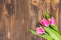 三朵桃红色花花束在右下角的在黑暗的木背景,题字的一个地方 库存图片