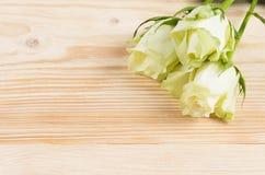 三朵白玫瑰在木背景说谎,为题字安置 库存照片