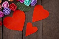 三朵红色心脏和花在棕色背景木头 免版税库存照片