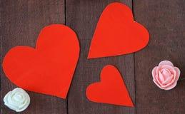 三朵红色心脏和花在棕色背景木头 免版税库存图片