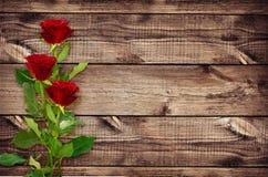 三朵红色玫瑰花浪漫花束在木头的 图库摄影