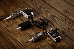 三杆纹身花刺枪在一张棕色木桌上安排了 免版税图库摄影