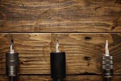 三杆纹身花刺枪在一张棕色木桌上安排了 库存照片