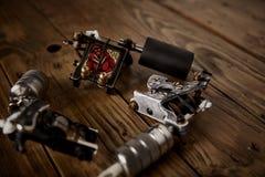 三杆纹身花刺枪在一张棕色木桌上安排了 图库摄影