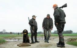 三条公猎人和狗用野兔 低透视图 农村的区 时数横向季节冬天 坐与抓住的骄傲的猎犬 免版税库存照片