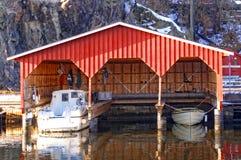 三条小船的红色木车库 库存照片