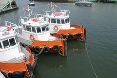 三条橙色猛拉小船 库存照片