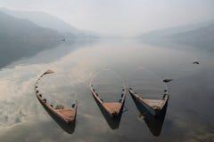 三条老木小船,一半淹没在水中,在小船下水剪影是可看见的,在mounta的背景中 库存照片