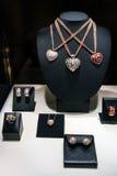三条项链由白色和玫瑰色金子制成在立场 与金刚石的心形的垂饰 套与圆环的豪华首饰和 库存照片