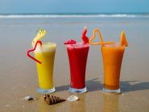 三杯与小管的自然果汁在海滨 免版税库存照片