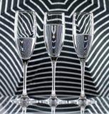 三杯在显示折射的黑条纹背景的水 帆布墙壁艺术 免版税库存图片