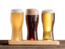 三杯在木桌上的啤酒 库存照片