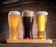 三杯在木桌上的啤酒 图库摄影
