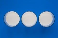 三杯在蓝色木书桌上的牛奶 免版税图库摄影