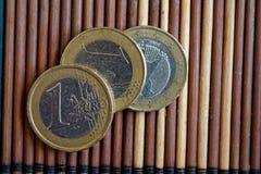 三枚欧洲硬币在木竹桌衡量单位说谎是1欧元 免版税图库摄影