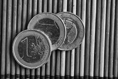 三枚欧洲硬币在木竹桌衡量单位说谎的黑白照片是一欧元 图库摄影