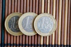 三枚欧洲硬币在木竹桌连续衡量单位说谎是一欧元 免版税库存图片
