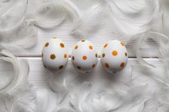 三根复活节彩蛋和羽毛在白色背景 免版税图库摄影