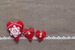 三根红色心脏和鞋带在粗麻布背景 免版税图库摄影
