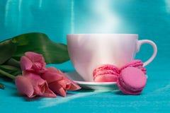三桃红色郁金香、一杯咖啡和三个桃红色蛋白杏仁饼干 库存照片