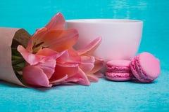 三桃红色郁金香、一杯咖啡和三个桃红色蛋白杏仁饼干 免版税库存照片