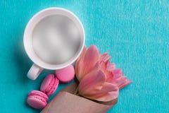 三桃红色郁金香、一杯咖啡和三个桃红色蛋白杏仁饼干 库存图片