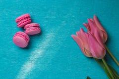 三桃红色郁金香和三个桃红色蛋白杏仁饼干 免版税库存图片