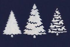 三棵白色圣诞节树绘与油漆通过在深蓝背景的一张钢板蜡纸 图库摄影