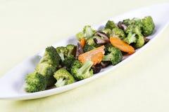 三棵菜(硬花甘蓝、蘑菇,红萝卜)在板材 免版税库存图片