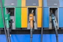 三气泵喷管前面在加油站的 免版税库存照片