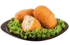 三油煎的面包炸肉排用在一个黑色的盘子的莴苣隔绝了白色背景 免版税库存照片