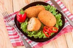 三油煎的面包炸肉排用在黑色的盘子和木背景的莴苣 库存图片