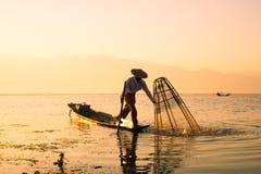 三渔夫抓住为在日出的食物钓鱼在Inle湖 库存照片