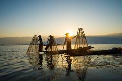 三渔夫抓住为在日出的食物钓鱼在Inle湖 免版税库存照片