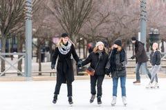 三滑冰在一个公开滑冰的溜冰场的愉快的少妇户外 库存图片
