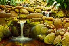 三瀑布在一个小池塘在庭院里 库存照片